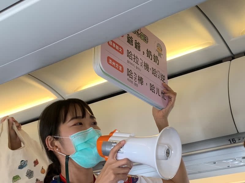 Guide holds signs on a Tigerair Taiwan flight that circles over South Korea's Jeju Island before returning to Taoyuan