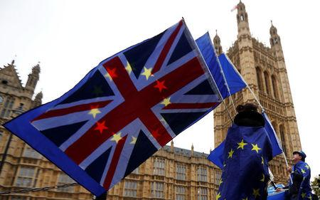 Anti-Brexit protesters wave EU and Union flags outside the Houses of Parliament in London
