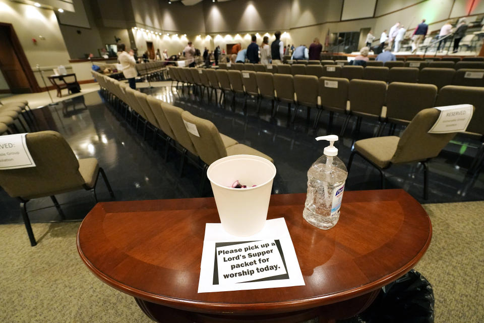 Congregants of Highland Colony Baptist Church are encouraged to spritz their hands with sanitizer before picking up a communion packet, while having a variety of seating options in the Worship Center of Highland Colony Baptist Church, Nov. 29, 2020, in Ridgeland, Miss. The church practices covid protocols by allowing families to sit spaced out from others, separating older and more vulnerable members in the worship hall and providing sanitizer and masks at the entrance. (AP Photo/Rogelio V. Solis)
