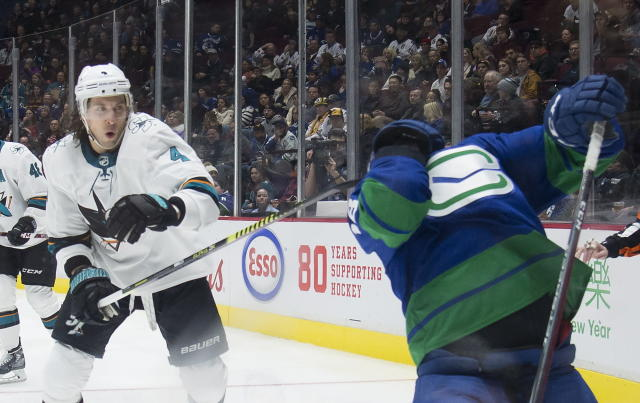 San Jose Sharks defenseman Brenden Dillon (4) high-sticks Vancouver Canucks right wing Jake Virtanen during the second period of an NHL hockey game Saturday, Jan. 18, 2020, in Vancouver, British Columbia. (Jonathan Hayward/The Canadian Press via AP)