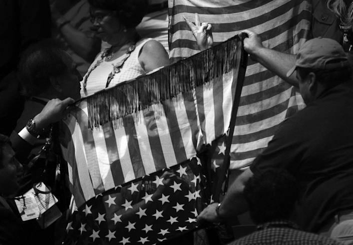 """<p>A protestor is blocked from the cameras by convention goers using American flag banners at the Republican National Convention Tuesday, July 19, 2016, in Cleveland, OH. She was advocating """"No Racism, No Hate"""". (Photo: Khue Bui for Yahoo News.</p>"""