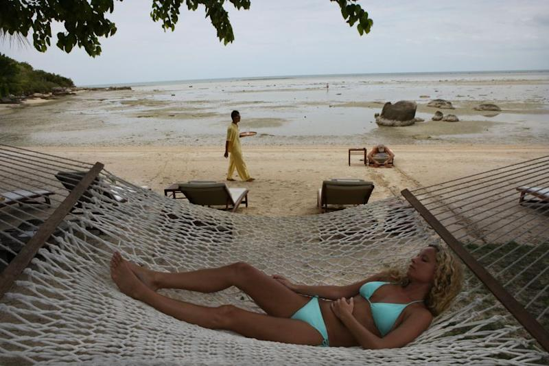 A woman rests on a hammock at the beach at the Kamalaya Wellness Sanctuary in Koh Samui, Thailand.