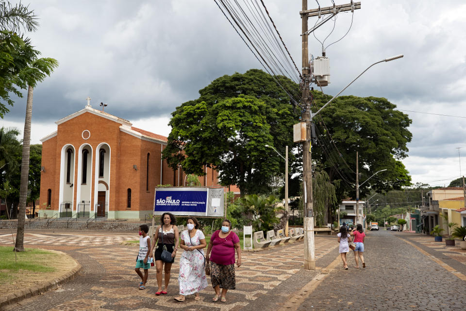A family walks in Serrana, Sao Paulo state, Brazil, Wednesday, Feb. 17, 2021. Brazil's Butantan Institute has started a mass vaccination on Wednesday of the city's entire adult population, about 30,000 people, to test the virus' behavior in response to the vaccine. (AP Photo/Andre Penner)