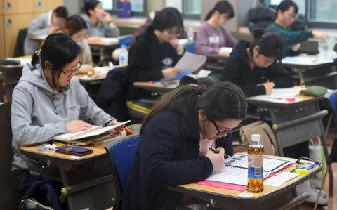 Students prepare to take the annual College Scholastic Ability Test, a standardised exam for college entrance, at a high school in Seoul on November 23, 2017 - Credit: AFP