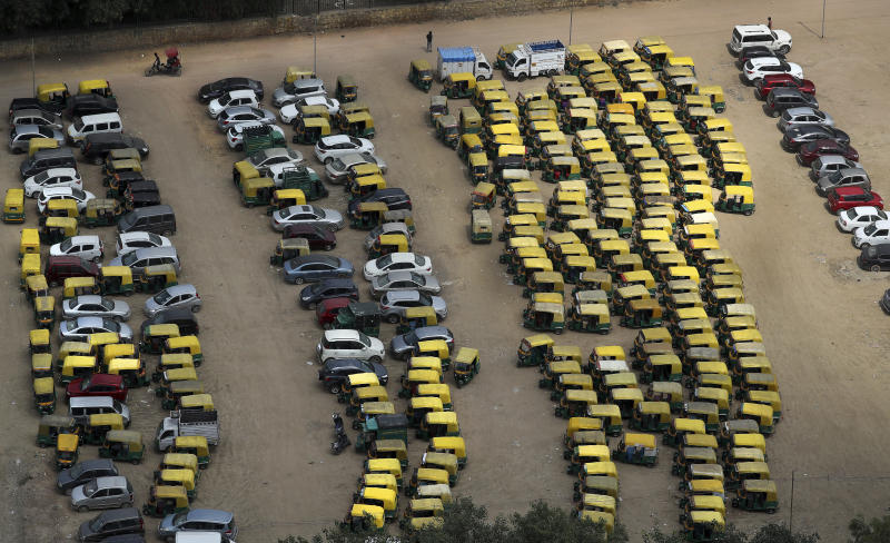 A rickshaw puller pedals past rows of auto-rickshaws and taxis parked during a public transport strike in New Delhi, India, Thursday, Sept. 19, 2019. Commuters in the Indian capital are facing problems as a large section of the public transport, including private buses, auto-rickshaws and a section of app-based cabs Thursday remained off the roads in protest against a sharp increase in traffic fines imposed by the government under a new law.(AP Photo/Manish Swarup)