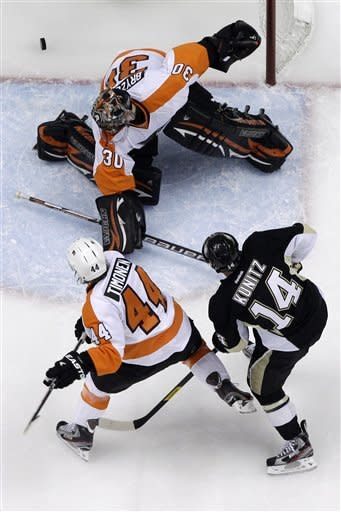 Pittsburgh Penguins' Chris Kunitz (14) wrists a first-period goal past Philadelphia Flyers goalie IIya Bryzgalov and defenseman Kimmo Timonen (44) during Game 2 of an opening-round NHL hockey playoff series in Pittsburgh, Friday, April 13, 2012. The Flyers won 8-5. (AP Photo/Gene J. Puskar)