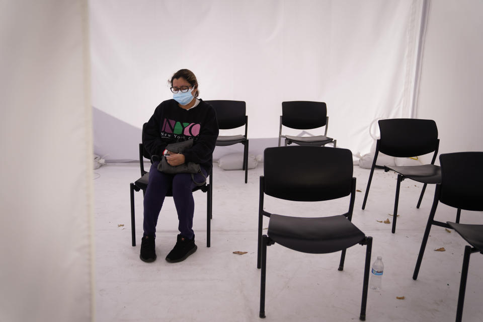 Margarita Hernandez, who tested positive for the coronavirus, waits in a tent to see a doctor for her allergic reaction to medication at Providence Holy Cross Medical Center in the Mission Hills section of Los Angeles, Tuesday, Dec. 22, 2020. (AP Photo/Jae C. Hong)