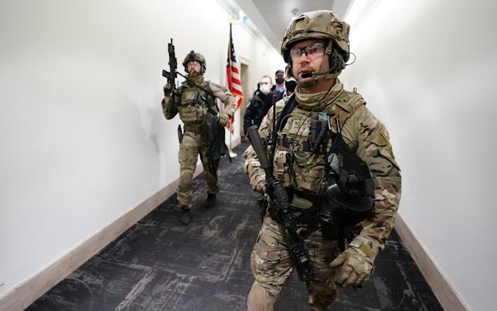 FBI agents armed with automatic weapons walk down a hallway in the U.S. Capitol  - KEVIN DIETSCH/UPI/Shutterstock /Shutterstock