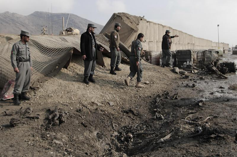 Afghan police examine remains after a suicide car bomb attack near a gate used by NATO troops in Kabul, Afghanistan, Wednesday, Dec. 11, 2013. The Afghan Interior Ministry says a car bomb has exploded near a gate used by NATO troops in the northern section of the Kabul airport. There were no casualties in the attack. (AP Photo/Rahmat Gul)