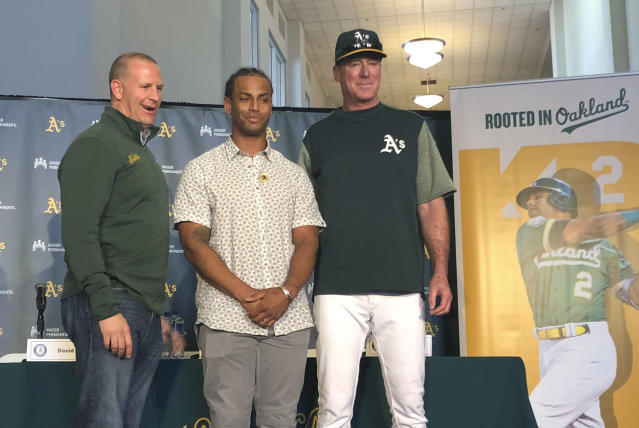 Oakland Athletics designated hitter Khris Davis, center, poses with general manager David Forst, left, and manager Bob Melvin, right, during a news conference about his contract extension Friday, April 19 2019, in Oakland, Calif. (AP Photo/Janie McCauley)