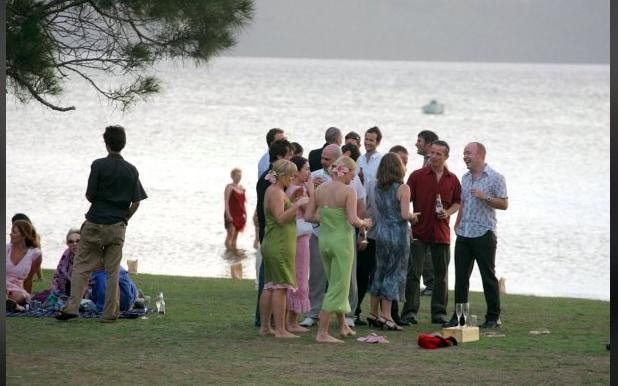 Guests gather at Sarah's lakeside wedding... and dip their toes in the water