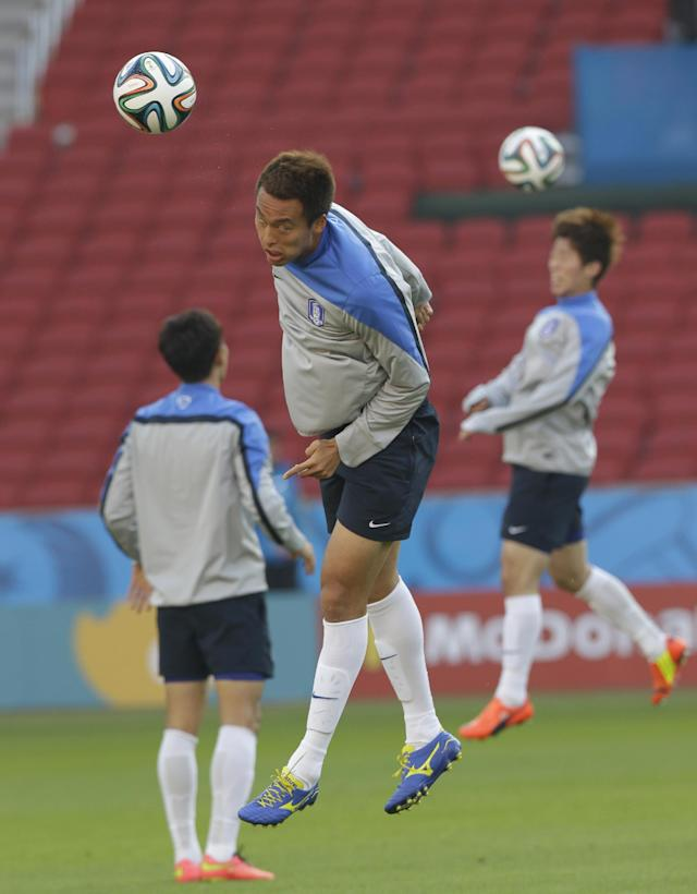 South Korea national soccer team player Kim Shin-wook, center, jumps to head the ball during an official training session the day before the group H World Cup soccer match between South Korea and Algeria at the Estadio Beira-Rio in Porto Alegre, Brazil, Saturday, June 21, 2014. (AP Photo/Lee Jin-man)