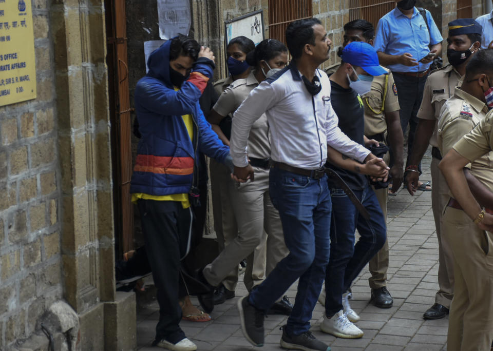 Bollywood actor Shah Rukh Khan's son Aryan Khan, left, is escorted by law enforcement officials outside the Narcotics Control Bureau (NCB) to appear before a court in Mumbai, India, Monday, Oct.4, 2021. (AP Photo)