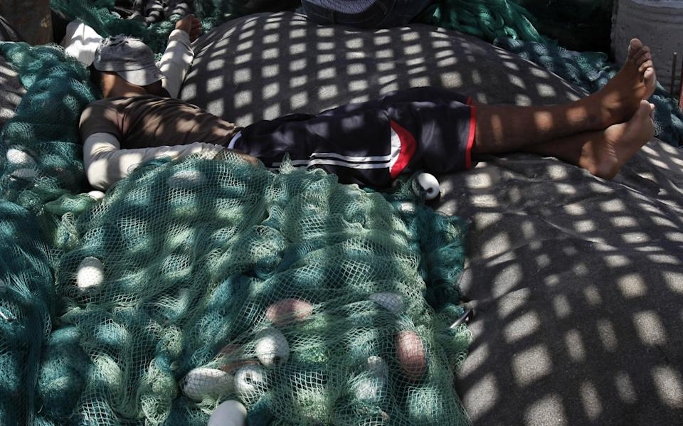 In this photo taken on Wednesday, July 31, 2013, a Palestinian fisherman sleeps on the net as he waits with others to refuel at the fishermen sea port in Gaza City. Regime change in Egypt has cost the Hamas rulers of Gaza their most important foreign ally, and ordinary Palestinians are being caught up in the animosity. Many Gazans were laid off after Egypt closed the territory's border, and Palestinians living in Egypt are keeping a low profile for fear of being targeted in the backlash against Hamas. (AP Photo/Adel Hana)