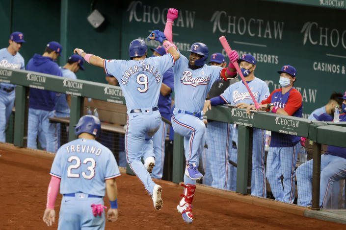 Texas Rangers Isiah Kiner-Falefa (9) celebrates with Adolis Garcia, right, after scoring on a double by Willie Calhoun during the fifth inning of a baseball game against the Seattle Mariners, Sunday, May 9, 2021, in Arlington, Texas. (AP Photo/Michael Ainsworth)