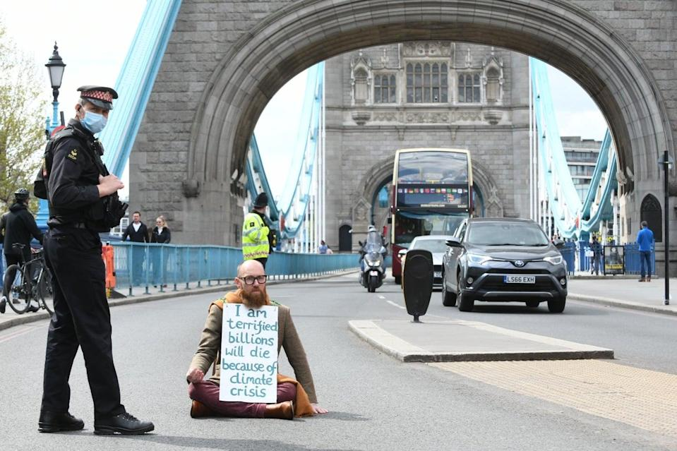 <p>Morgan Trowland, 38, blocking traffic on Tower Bridge as part of an Extinction Rebellion protest </p> (PA)