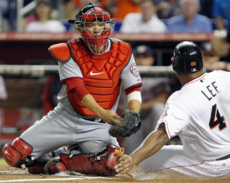 Miami Marlins' Carlos Lee, right, slides safely into home as Washington Nationals catcher Kurt Suzuki attempts the tag during the first inning of a baseball game, Tuesday, Aug. 28, 2012, in Miami. Lee scored on a single by Giancarlo Stanton. (AP Photo/Wilfredo Lee)