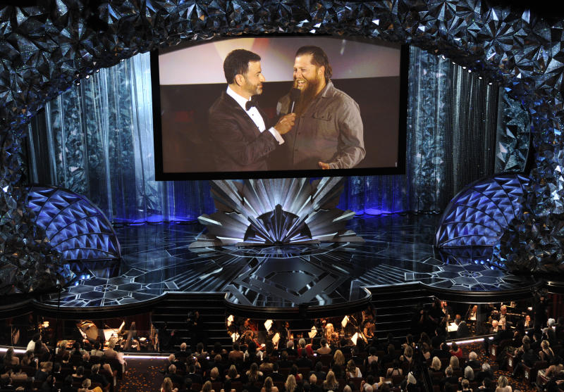 Host Jimmy Kimmel, left, speaks with a member of the movie theater audience