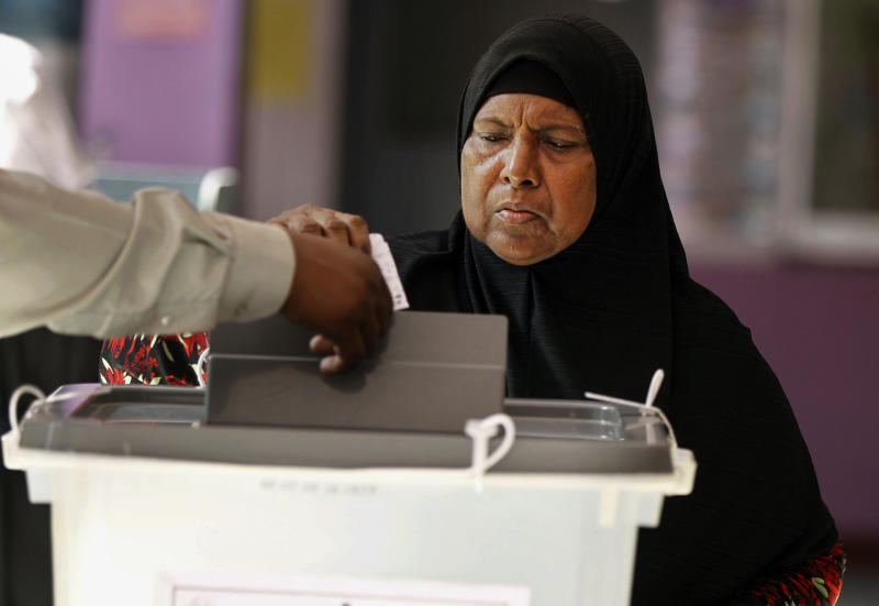 A Maldivian woman casts her vote in Male, Maldives, Saturday, Nov. 9, 2013. After two months of political bickering and repeated failure to hold an election, Maldives voters headed to polling stations Saturday to elect a new president for their vulnerable new democracy. (AP Photo/Sinan Hussain)