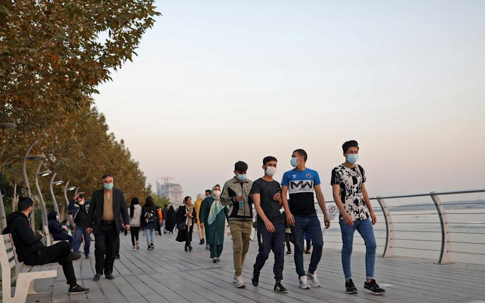 Iranian people wearing masks walk at a promenade in West Tehran - Majid Asgaripour/WANA