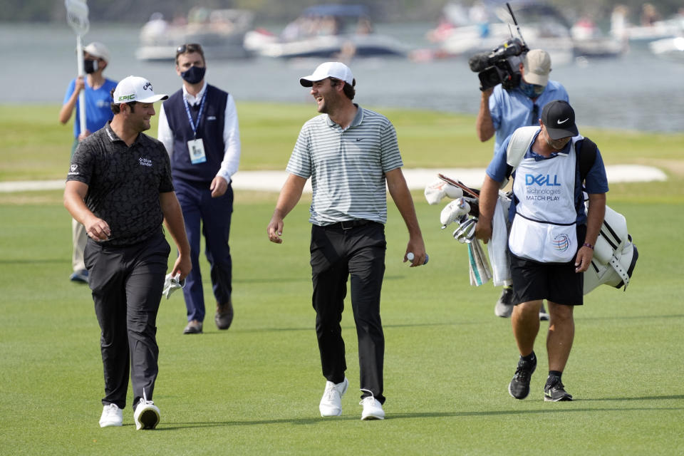 Jon Rahm, of Spain, left, and Scottie Scheffler, center, walk up the No. 14 fairway during a round of eight match at the Dell Technologies Match Play Championship golf tournament Saturday, March 27, 2021, in Austin, Texas. (AP Photo/David J. Phillip)
