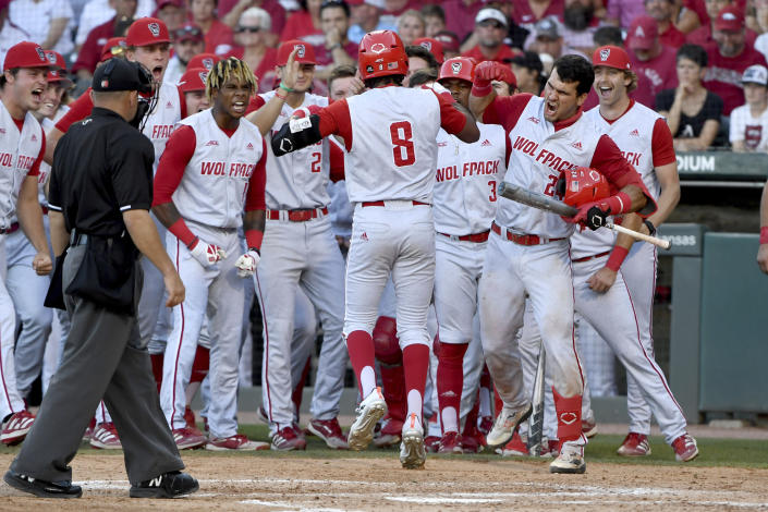 North Carolina State's Jose Torres (8) is greeted by teammates after hitting a go-ahead home run against Arkansas in the ninth inning of an NCAA college baseball super regional game, Sunday, June 13, 2021, in Fayetteville, Ark. (AP Photo/Michael Woods)