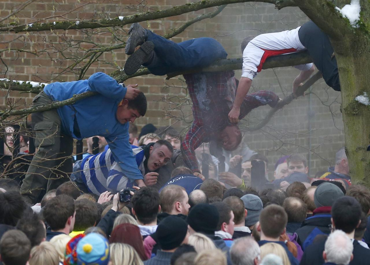 <p>Desperate players climb a tree and hang from the branches in a bid to remove the ball from the hug. The game resembles a disorganised rugby scrum (Reuters)</p>