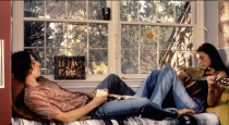 <p>Set in the 1970s, <em>Dazed and Confused</em> perfectly captured the bohemian style of the era. Case in point, Milla Jovovich in flared patchwork jeans while strumming on an acoustic guitar. </p>