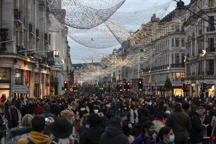FILE - In this Saturday, Dec. 12, 2020 file photo crowds of shoppers walk under the Christmas lights in Regent Street, in London. (AP Photo/Alberto Pezzali, File)