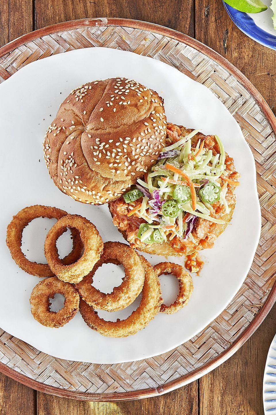 """<p>With onion rings and a homemade okra slaw, sloppy joes become a bit more refined.</p><p><strong><a href=""""https://www.countryliving.com/food-drinks/recipes/a44280/sloppy-joes-pickled-okra-slaw-recipe/"""" rel=""""nofollow noopener"""" target=""""_blank"""" data-ylk=""""slk:Get the recipe"""" class=""""link rapid-noclick-resp"""">Get the recipe</a>.</strong></p>"""