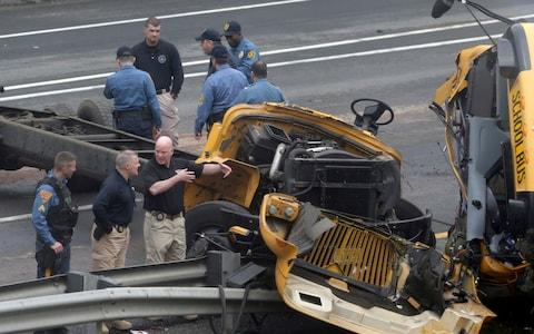 Emergency personnel examine the school bus after the collision - Credit: Seth Wenig/AP