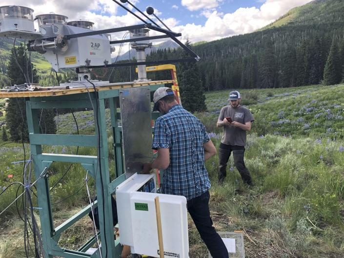 In this July 1, 2021, provided by Lawrence Berkeley National Laboratory, Heath Powers, center, site manager for the second Atmospheric Radiation Measurement mobile facility, helps set up radiometers for ARM's Surface Atmosphere Integrated Field Laboratory (SAIL) field campaign in Gothic, Colo. Federal scientists are launching an effort to better understand the hydrology in the U.S. West. The U.S. Department of Energy on Tuesday, Aug. 24 announced a new kind of climate observatory near the headwaters of the Colorado River. (David Chu/Lawrence Berkeley National Laboratory via AP)
