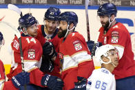 Florida Panthers center Alex Wennberg (21) is congratulated by left wing Grigori Denisenko (14), defenseman Radko Gudas (7) and defenseman Keith Yandle (3) after scoring a goal during the third period of an NHL hockey game against the Tampa Bay Lightning, Monday, May 10, 2021, in Sunrise, Fla. (AP Photo/Lynne Sladky)