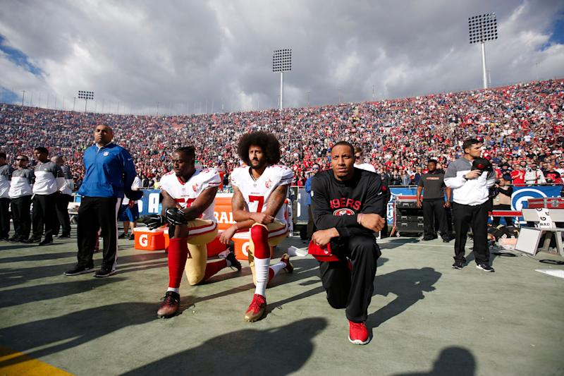 Eli Harold #58, Colin Kaepernick #7 and Eric Reid #35 of the San Francisco 49ers kneel on the sideline, during the anthem, prior to the game against the Los Angeles Rams at the Los Angeles Coliseum on December 24, 2016 in Los Angeles, California.