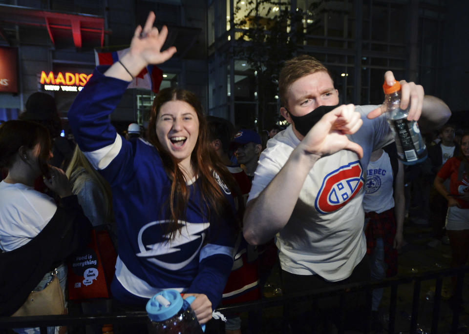 A Tampa Bay Lightning fan and a Montreal Canadiens fan react as they watch coverage of the end of Game 5 of the NHL hockey Stanley Cup Finals, outside the Bell Centre in Montreal on Wednesday, July 7, 2021. (Ryan Remiorz/The Canadian Press via AP)