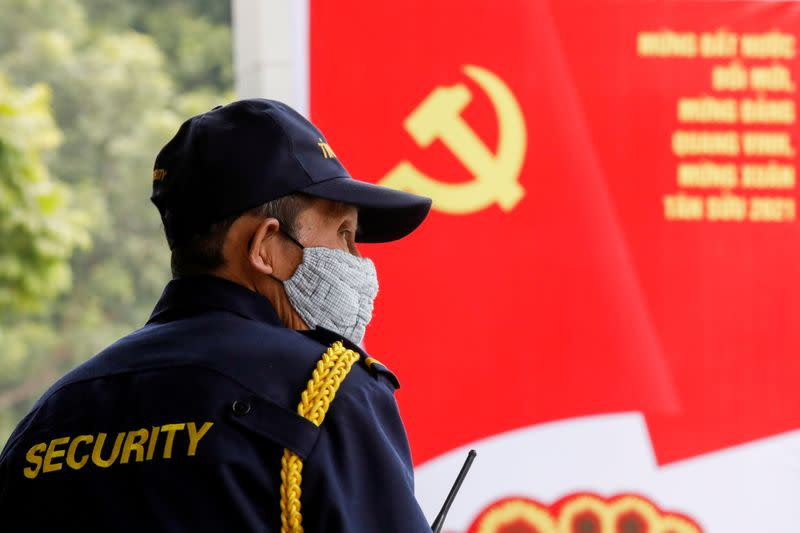 FILE PHOTO: A security officer stands guard near a poster for the upcoming 13th National Congress of the ruling Communist Party of Vietnam