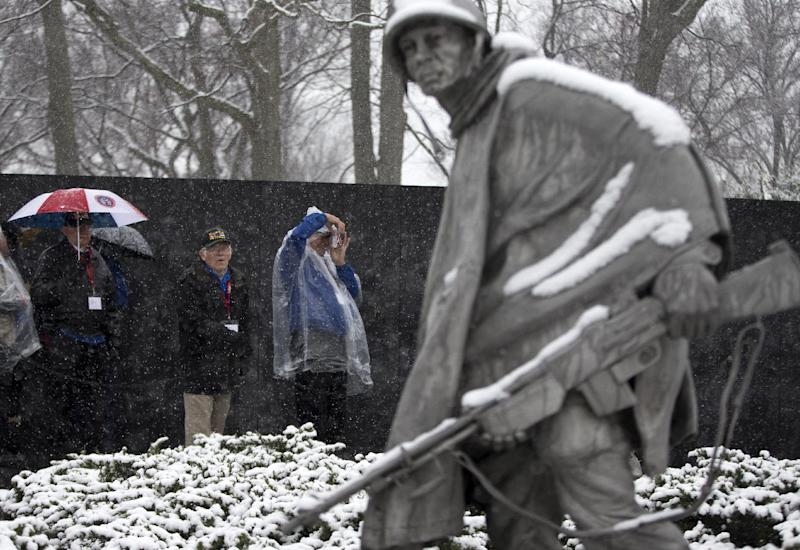 Visitors view the Korean War Memorial during a snow storm in Washington, Tuesday, March 25, 2014. The calendar may say it's spring, but the mid-Atlantic region is seeing snow again. The National Weather Service has issued a winter weather advisories for much of the region Tuesday. The advisories warn that periods of snow could make travel difficult, with slippery roads and reduced visibility. (AP Photo/ Evan Vucci)