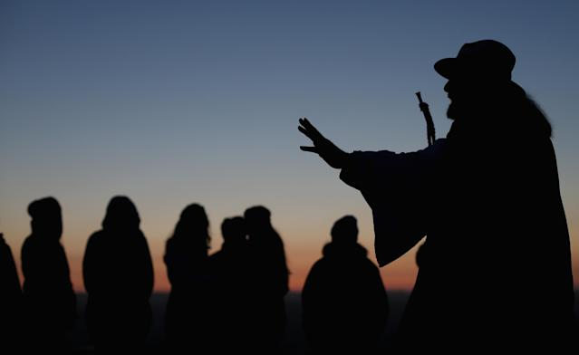 GLASTONBURY, ENGLAND - MAY 01: Rollo Maughfling, (R) the Archdruid of Glastonbury and Stonehenge conducts a Beltane dawn celebration service in front of St. Michael's Tower on Glastonbury Tor on May 1, 2013 in Glastonbury, England. Although more synonymous with International Workers' Day, or Labour Day, May Day or Beltane is celebrated by druids and pagans as the beginning of summer and the chance to celebrate the coming of the season of warmth and light. Other traditional English May Day rites and celebrations include Morris dancing and the crowning of a May Queen with celebrations involving a Maypole. (Photo by Matt Cardy/Getty Images)