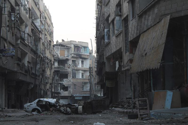 A damaged vehicle and barricade block a deserted street in the Harasta area in eastern al-Ghouta, near Damascus