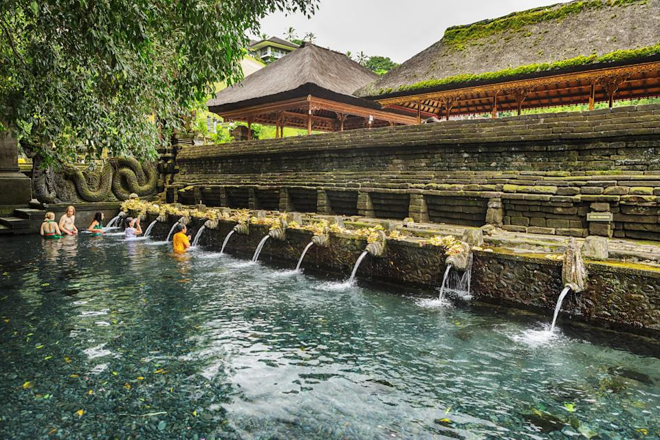 """<p><strong>What's the history behind this place?</strong><br> Tirta Empul (""""Holy Spring""""), an important sacred water temple for more than 1,000 years, contains a warren of shrines, gates, courtyards, and purification pools where Balinese Hindus """"baptize"""" themselves underneath a succession of waterspouts. Equally popular with travelers, the temple commands a 15,000 rupiah ($1) entry fee and the wearing of a sarong.</p> <p><strong>Any particular highlights?</strong><br> There's something about the ancient fountain pools that feels especially moving.</p> <p><strong>What's the best way to get around?</strong><br> You can explore alone but you might be happier hiring a guide.</p> <p><strong>Who else are we likely to spot here?</strong><br> Tourists spending a leisurely hour or so walking the grounds and taking in the beauty.</p> <p><strong>Anything else we should know before visiting?</strong><br> Yes, there are crowds, but the ornate temples, exquisite stone statues of the divine, and sacred bathing pools are inspiring nonetheless. Want to immerse yourself (literally) in the holy Tirta Empul experience? Bring an additional change of clothes and swimwear to partake in the water ritual; helpful temple staff are on-hand to explain the protocol if you came without a guide. However, these days the water isn't the cleanest.</p> <p><strong>Why would you recommend this place?</strong><br> Despite its popularity, Tirta Empul contains a rare spiritual heft not seen in other Balinese temples. Come to feel moved.</p>"""