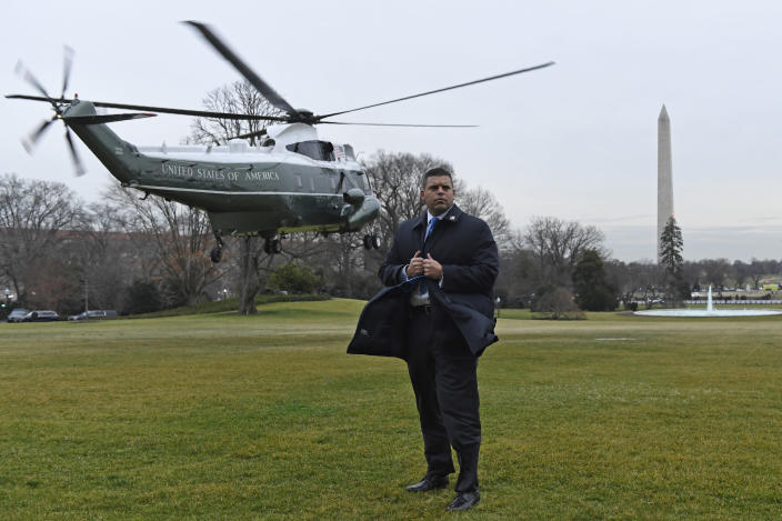 A U.S. Secret Service agents holds on to his coat as Marine One, with President Donald Trump and first lady Melania Trump on board, lifts off from the South Lawn of the White House in Washington, Monday, Jan. 13, 2020. The Trumps are heading to New Orleans to attend the College Football Playoff National Championship between Louisiana State University and Clemson. (AP Photo/Susan Walsh)