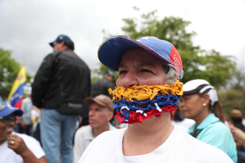 An opponent of the Nicolas Maduro government, his mouth covered with strands representing the national colors of Venezuela, waits for the arrival of opposition leader Juan Guaidó to lead a rally in Caracas, Venezuela, Saturday, May 11, 2019. Guaidó has called for nationwide marches protesting the Maduro government, demanding new elections and the release of jailed opposition lawmakers. (AP Photo/Martin Mejia)
