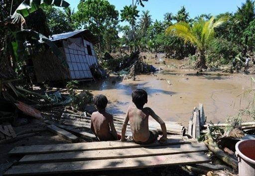 Two boys look at a destroyed house in Iligan City. The death toll from a destructive storm that hit the southern Philippines has risen to 927 as bodies surfaced in the sea, the head of the government disaster monitoring council said Tuesday