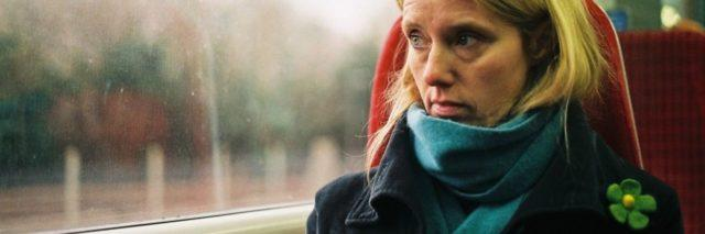 photo of woman looking serious looking out of window on train