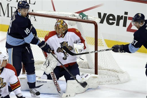 Pittsburgh Penguins center Sidney Crosby (87) can't get a shot past Florida Panthers goalie Jacob Markstrom (35) with Penguins center Brandon Sutter (16) looking for a rebound during the first period of an NHL hockey game in Pittsburgh Friday, Feb. 22, 2013. (AP Photo/Gene J. Puskar)