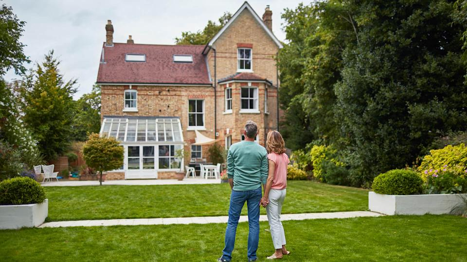 Rear view of mature couple looking at house.