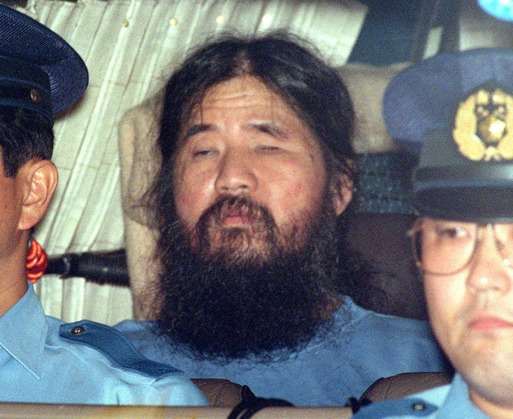 Japanese doomsday cult leader Shoko Asahara center sits in a police van following an interrogation in Tokyo. Japanese media reports say on Friday
