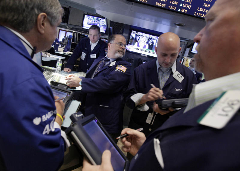 In this Friday, June 22, 2012, photo, specialist Douglas Johnson, center, works with traders at his post on the trading floor of the New York Stock Exchange. Wall Street's open Wednesday June 27, 2012 is not expected to alter the market mood, with both Dow futures and the broader S&P 500 futures down 0.1 percent.   (AP Photo/Richard Drew)
