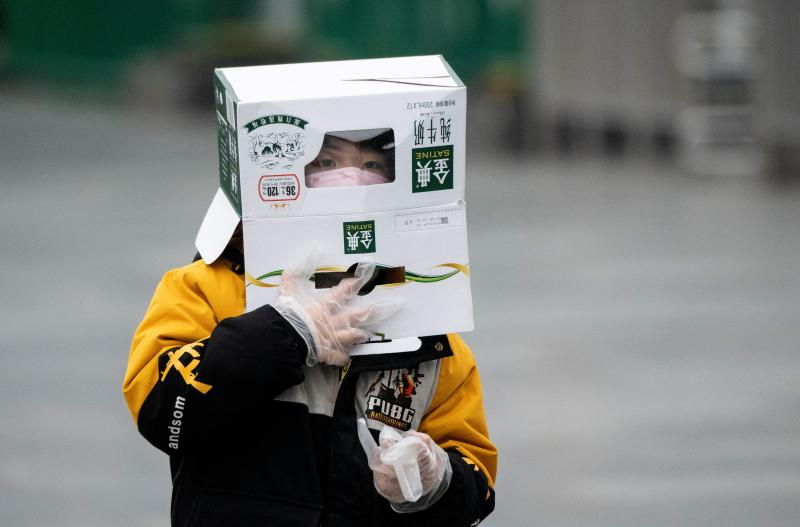 A boy wears a cardboard box on his head at the Shanghai Railway station in Shanghai on February 13, 2020. - The number of deaths and new cases from China's COVID-19 coronavirus outbreak spiked dramatically on February 13 after authorities changed the way they count infections in a move that will likely fuel speculation that the severity of the outbreak has been under-reported. (Photo by NOEL CELIS / AFP) (Photo by NOEL CELIS/AFP via Getty Images)