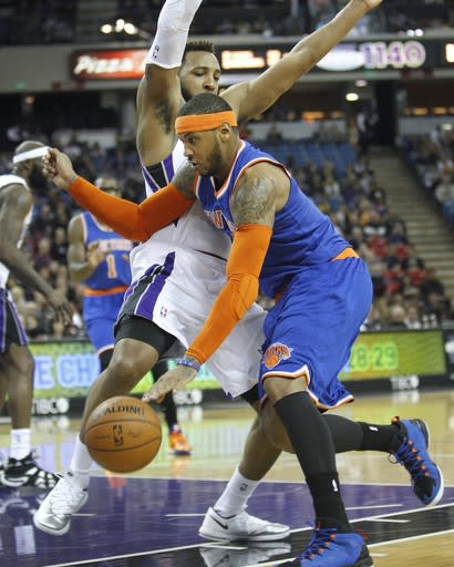 New York Knicks forward Carmelo Anthony, right, drives to the basket against Sacramento Kings defender Derrick Williams during the first half of an NBA basketball game in Sacramento, Calif., on Wednesday, March 26, 2014.(AP Photo/Steve Yeater)